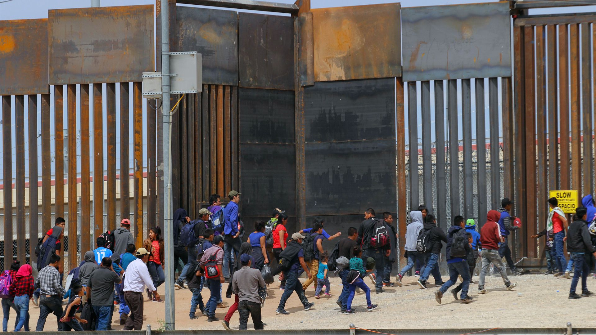 Immigrants crowding a border wall at the U.S. southern border.