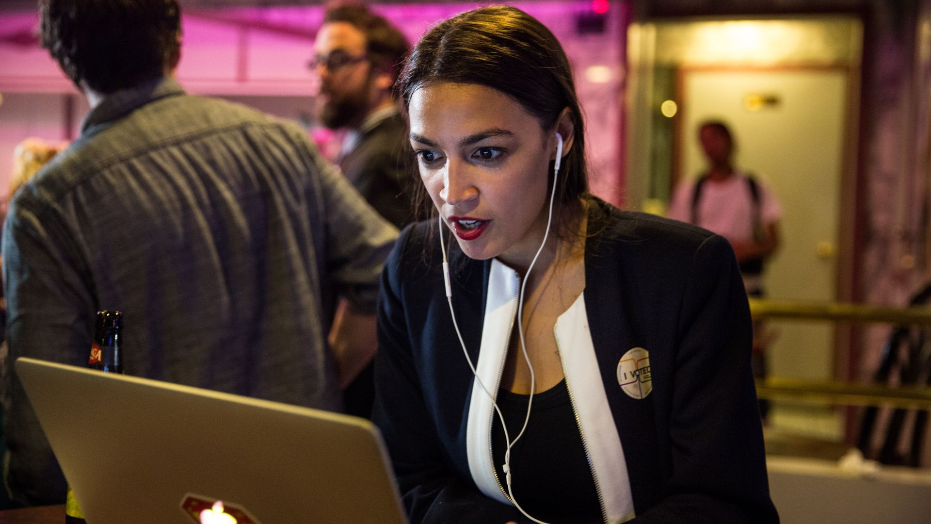Alexandria Ocasio-Cortez looking at a laptop.