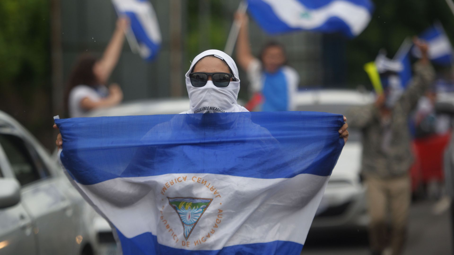 A demonstrator holds a Nicaraguan flag during the march in cars and motorcycles from Managua to Ticuantepe, 15km south of Managua.