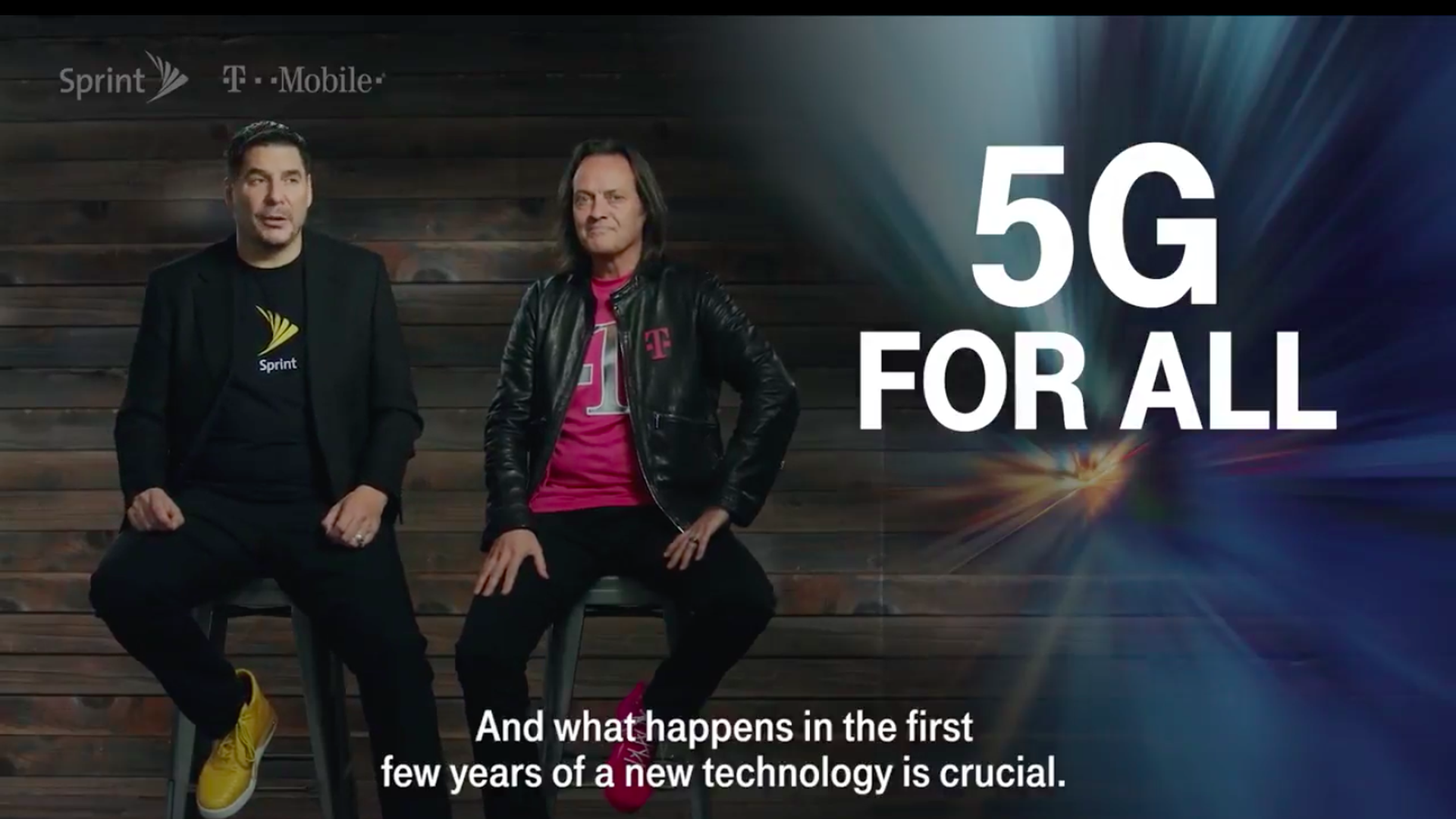 Sprint and T-Mobile CEOs sit on chairs next to a big graphic that says 5G for all