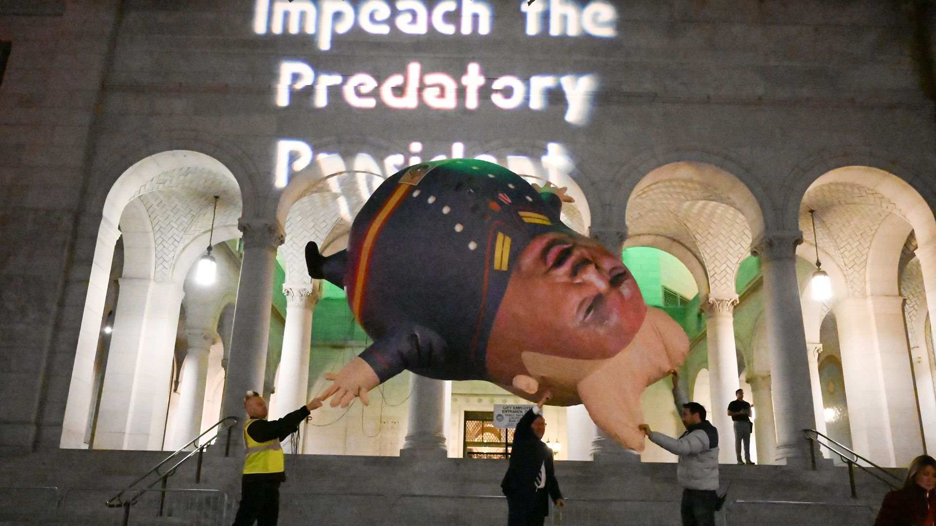 """rotestors prepare to release a """"Comrade Trump"""" balloon at a demonstration in support of his impeachment in downtown Los Angeles"""