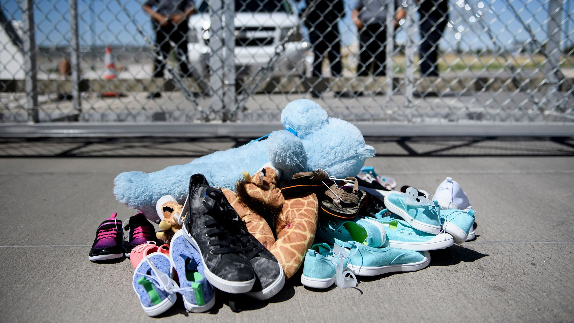 A pile of toys and small shoes in front of a chain link fence near the border.