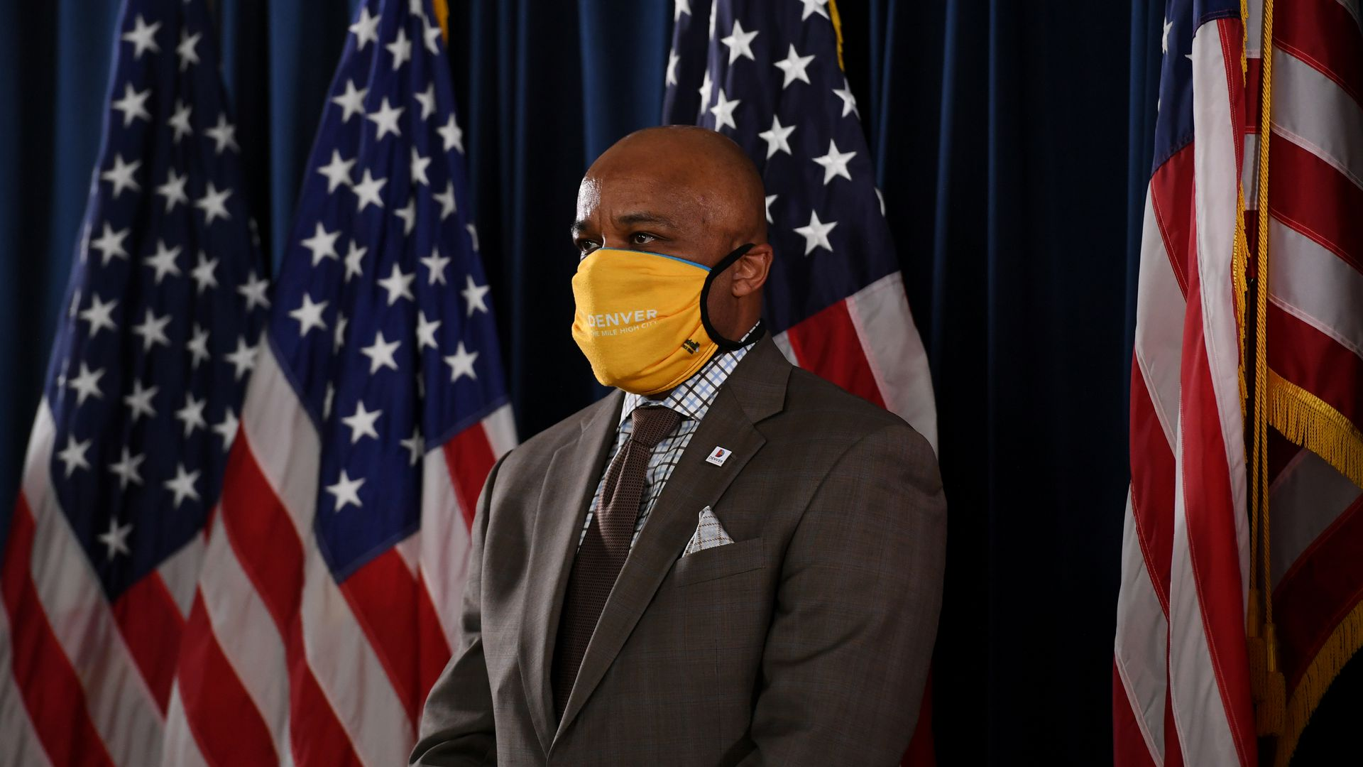 A photo of Denver Mayor Michael Hancock wearing a mask and standing in front of several American flags.