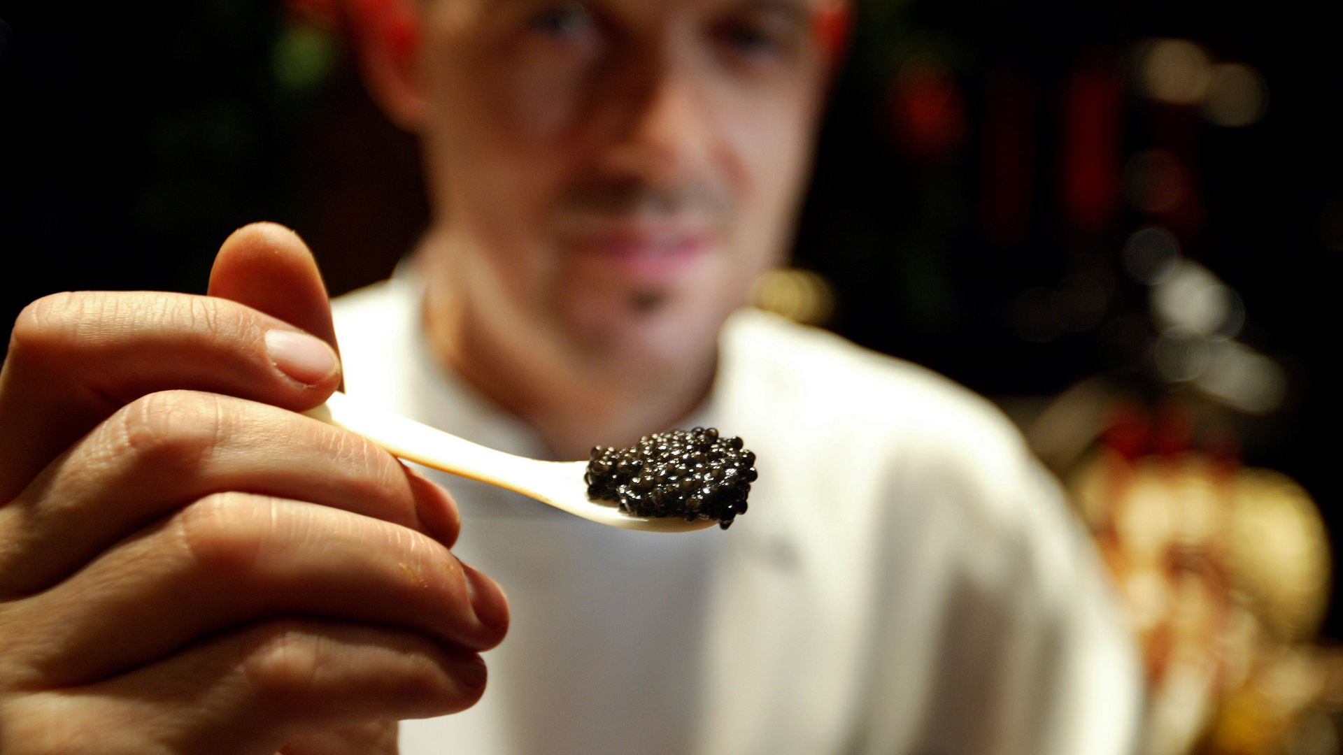 A man holds up caviar on a spoon.
