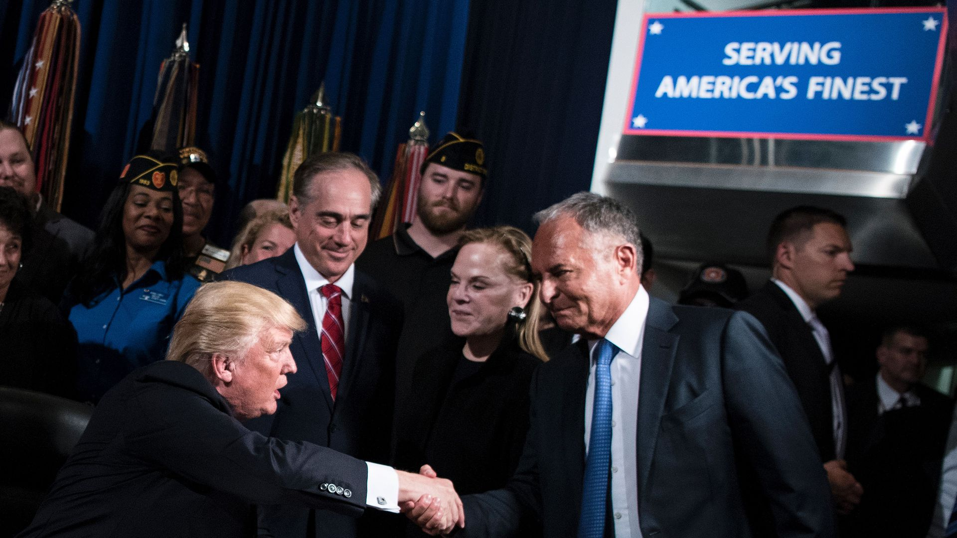 Trump shaking hands with Ike Perlmutter with David Shulkin looking on