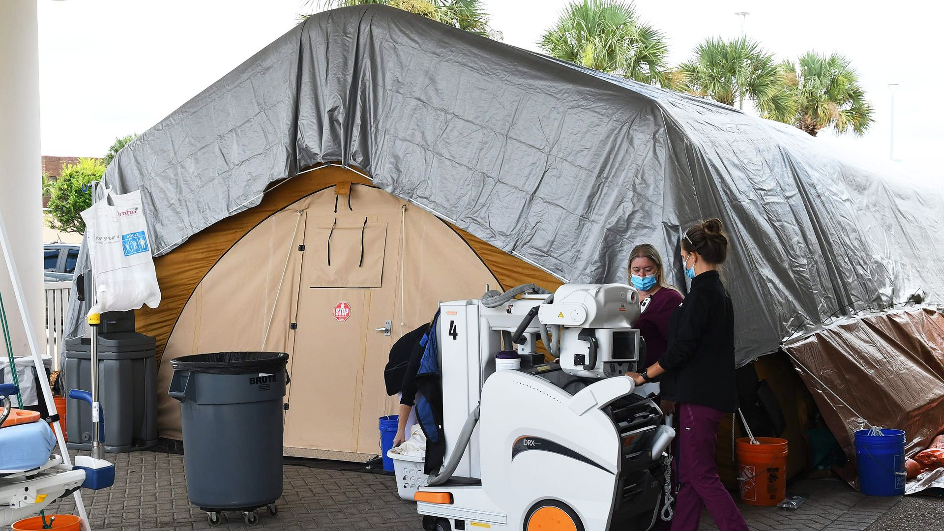 Nurses bring a portable x-ray machine to a treatment tent outside the emergency department at Holmes Regional Medical Center in Melbourne, Fla., July 29