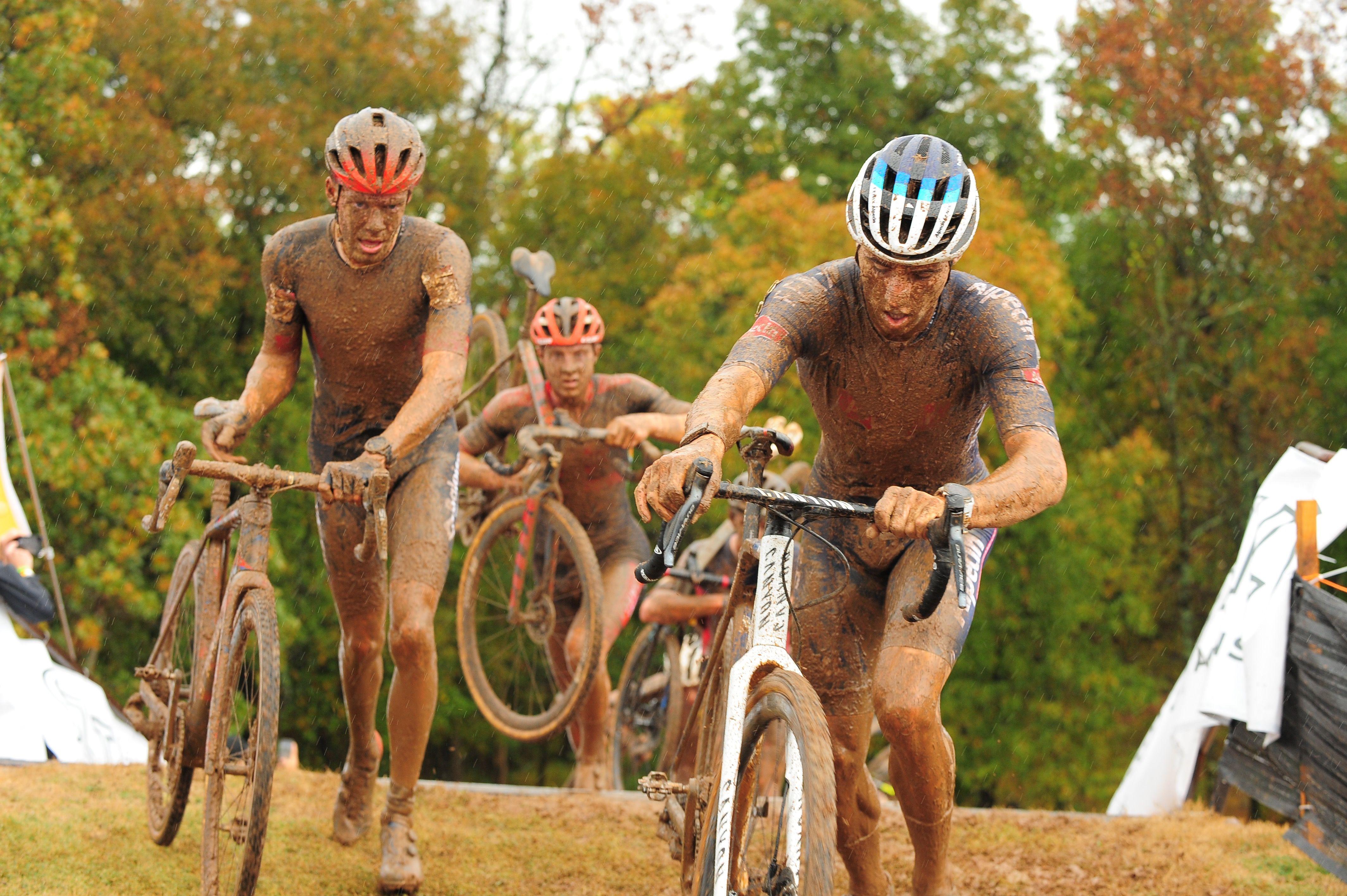 Photo of three muddy men getting on bikes.