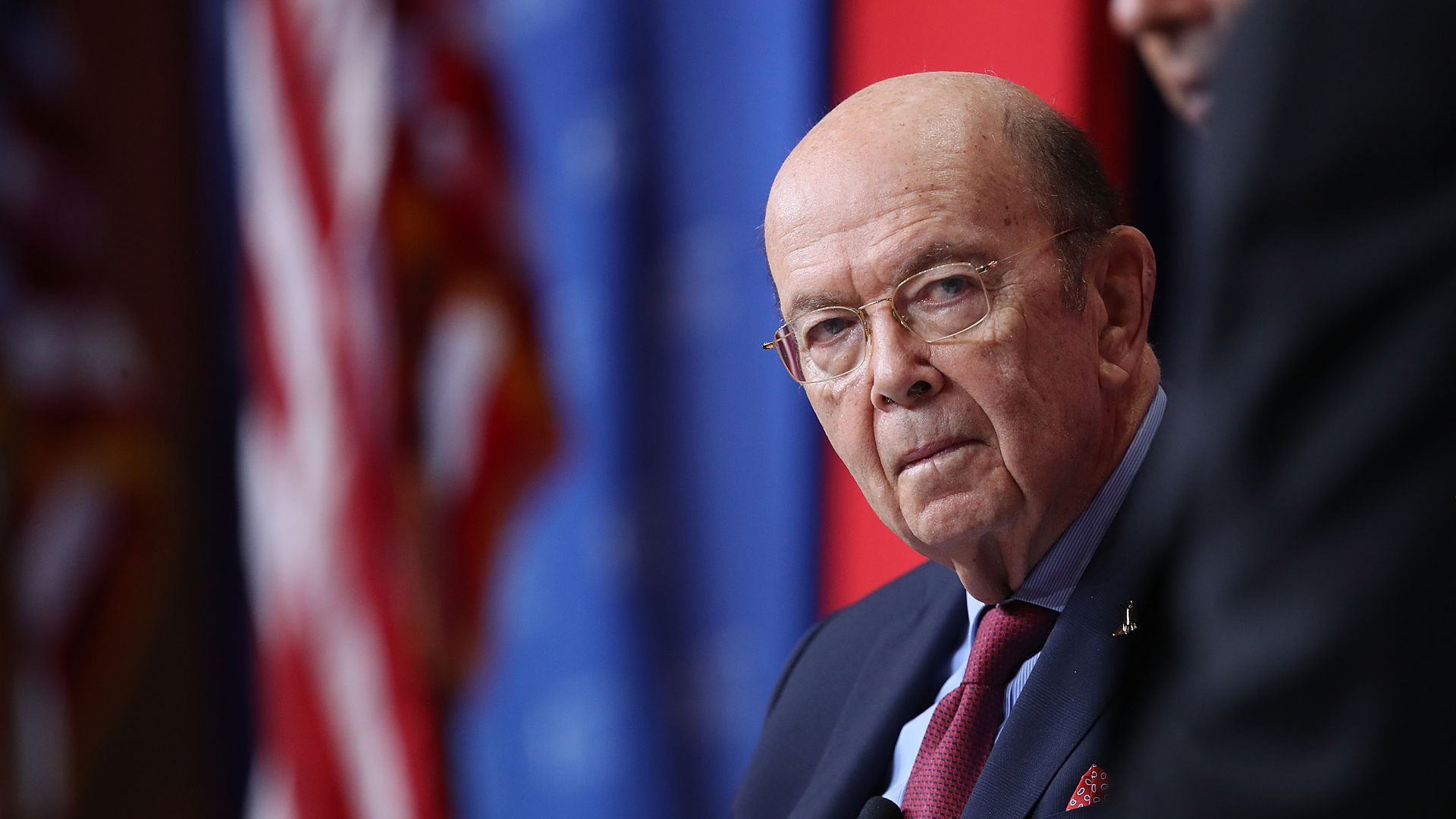 Wilbur Ross in front of an American flag