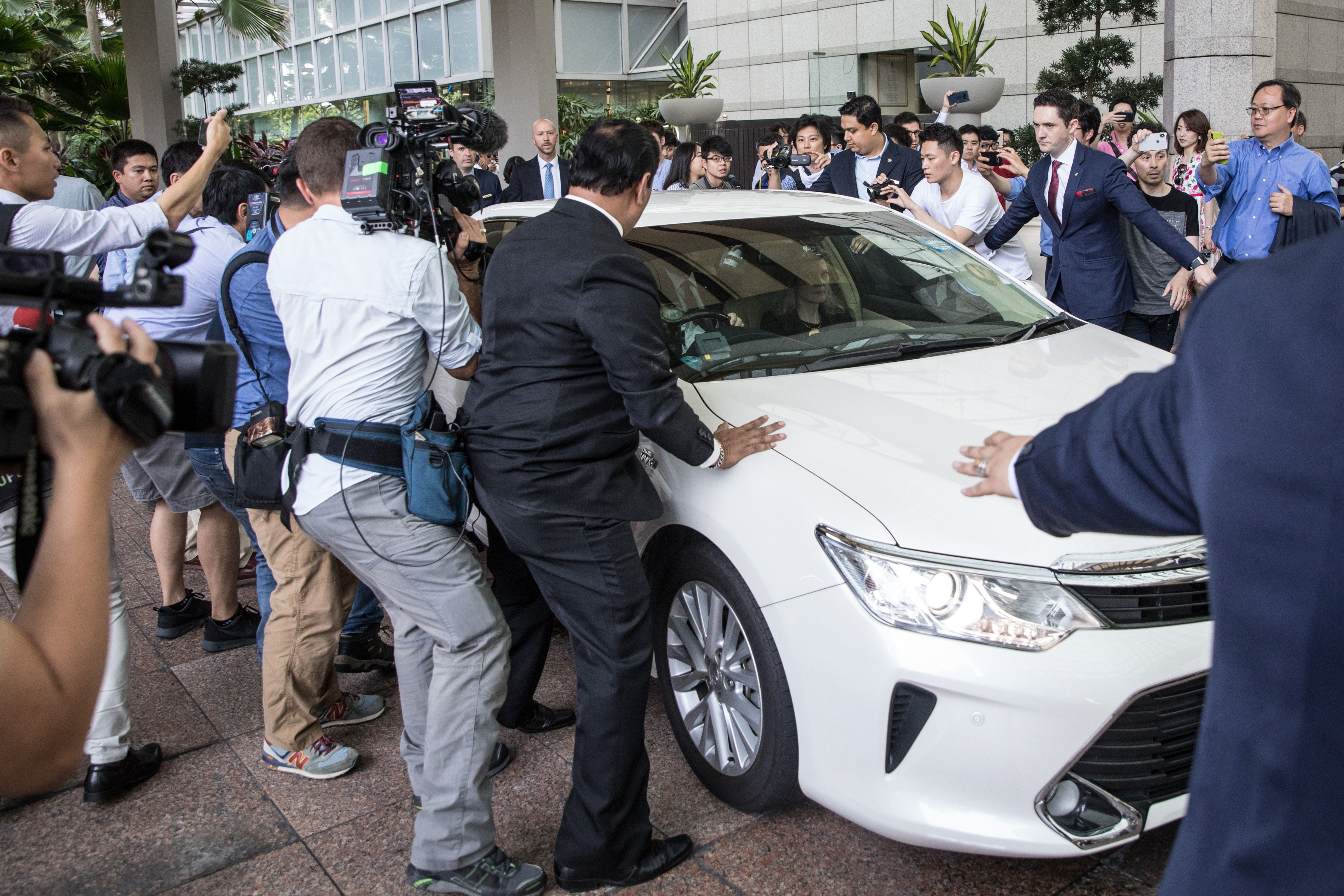 Security officers and press surround a limo in Singapore