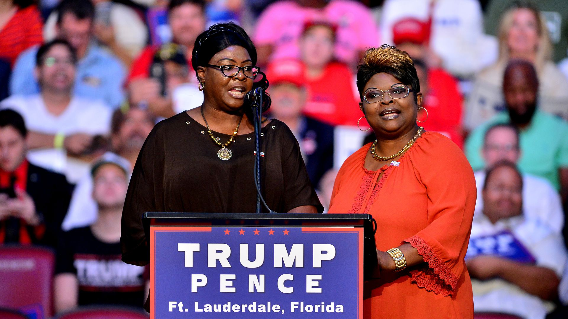 Diamond and Silk speak on stage at a Trump rally