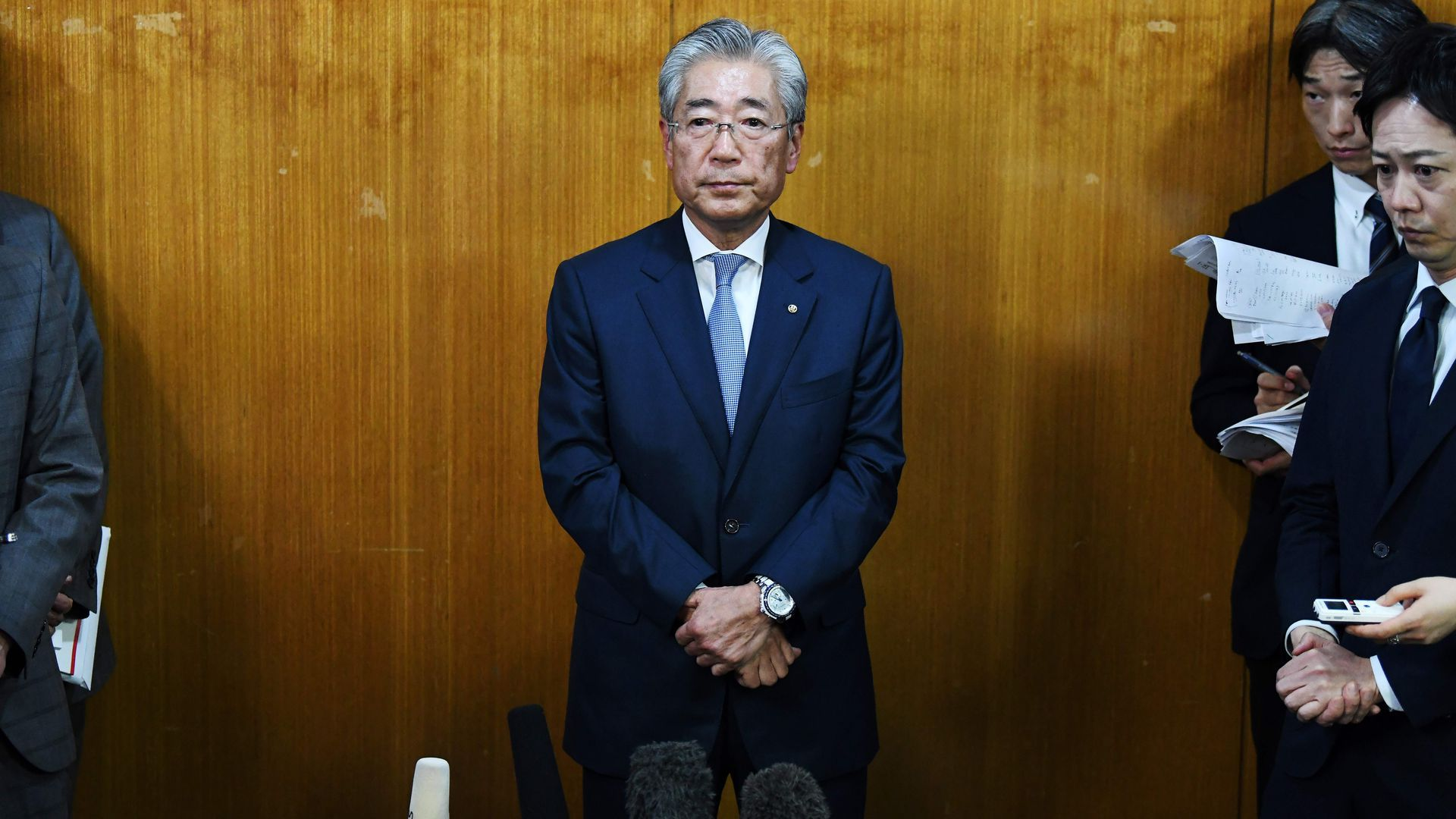 Tsunekazu Takeda stands in a blue suit with his arms folded and stands against a wooden wall.