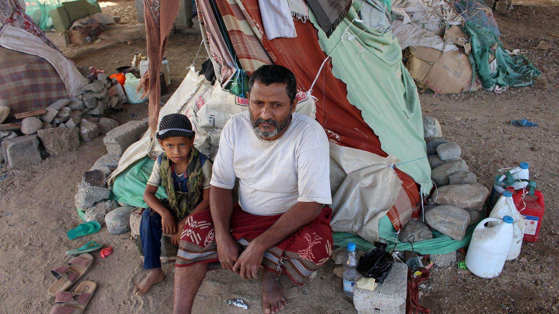 Displaced Yemenis sit under a makeshift shelter at a camp for internally displaced persons.
