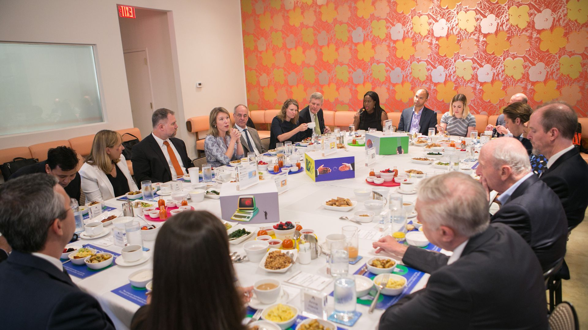 A large table with Kim Hart and 25 experts gathered for a conversation over breakfast