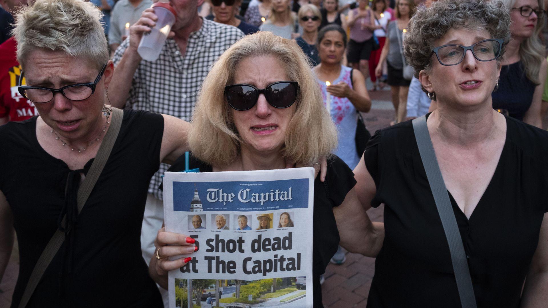 Three women marching at vigil.