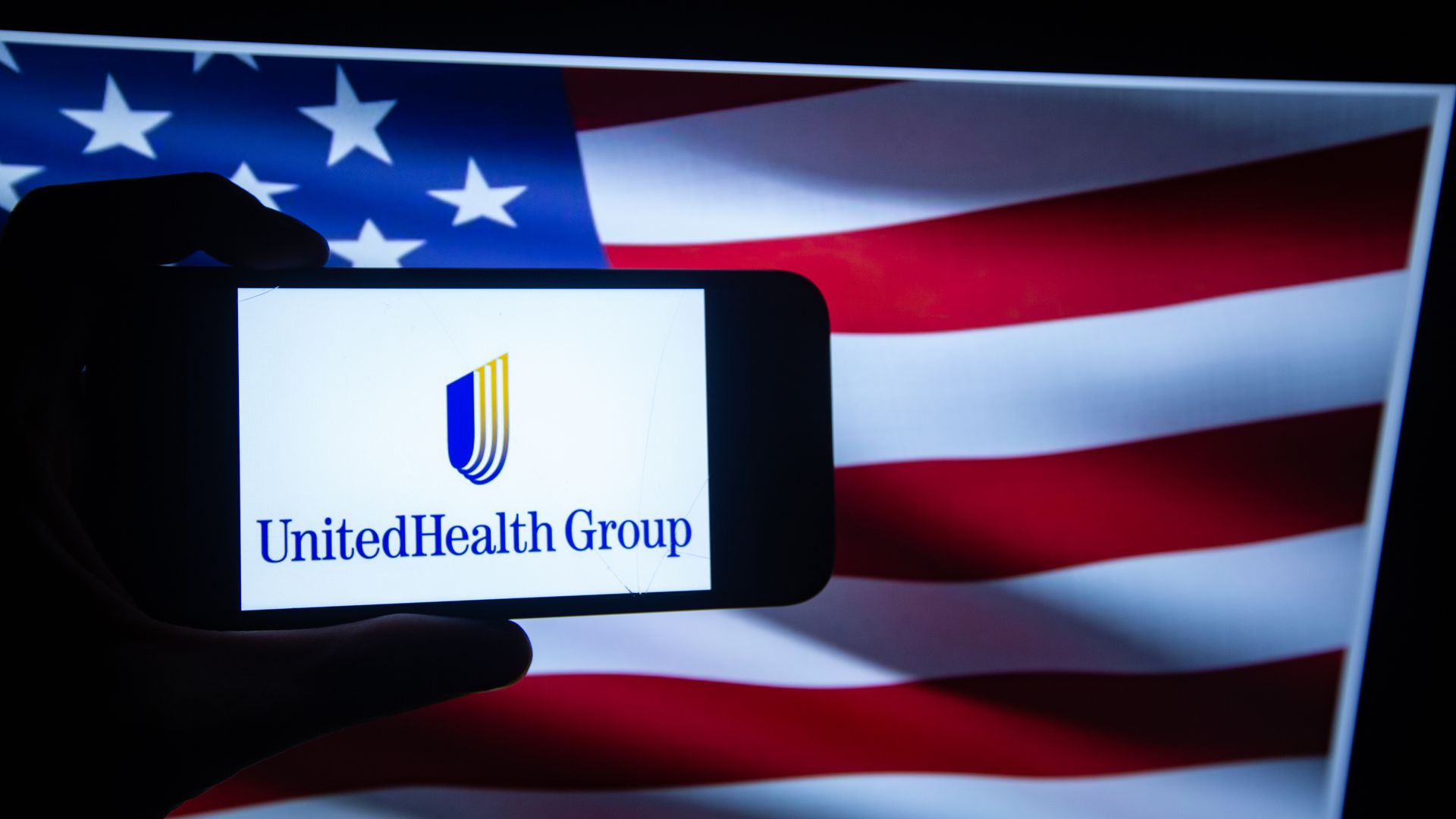 MAn holding phone that has united health group logo on it