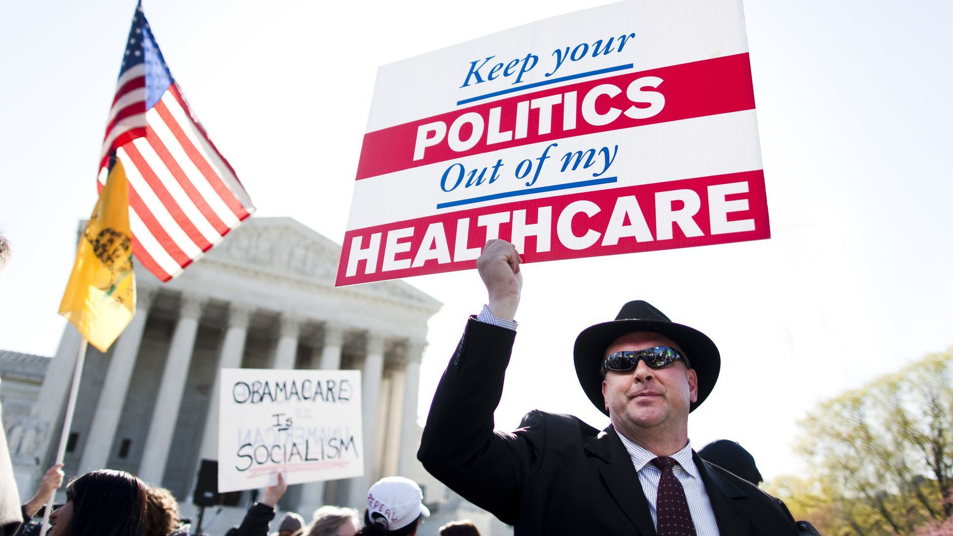 Protesters outside the Supreme Court waving signs about the ACA