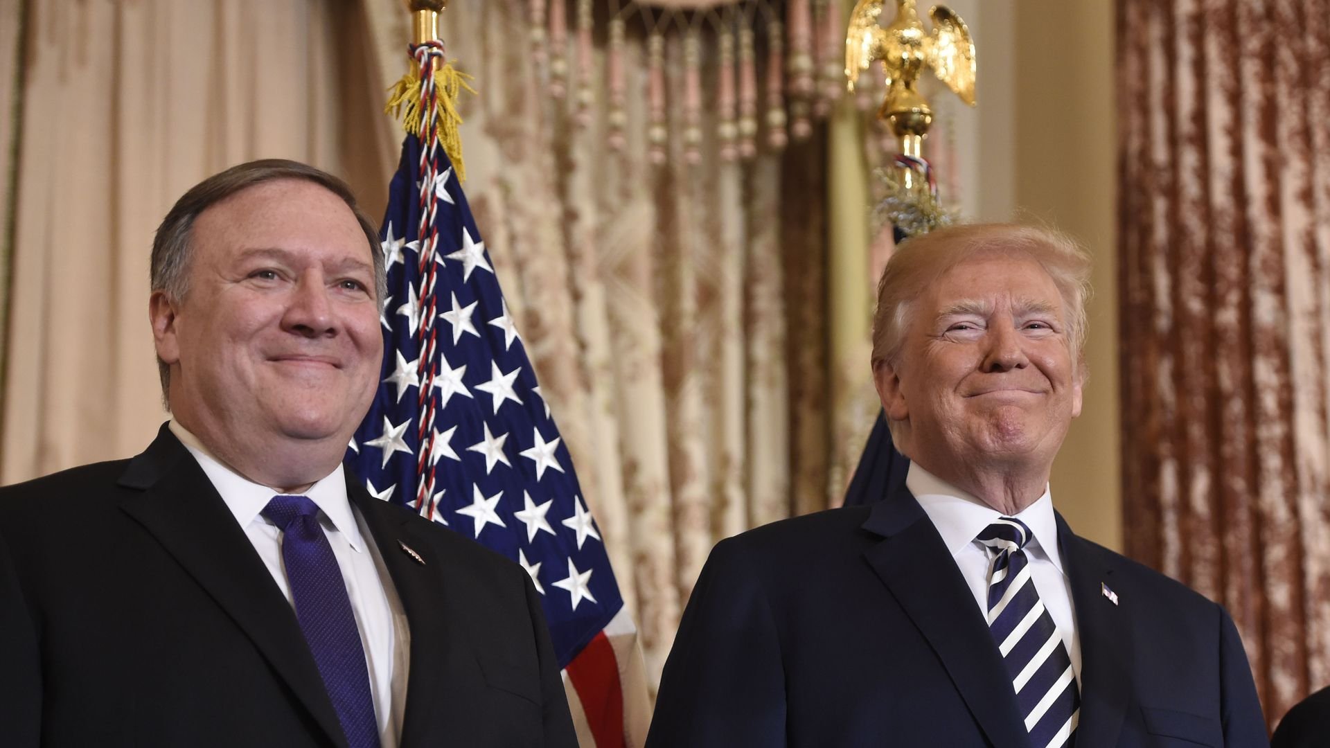 Mike Pompeo and Trump stand before an American flag.