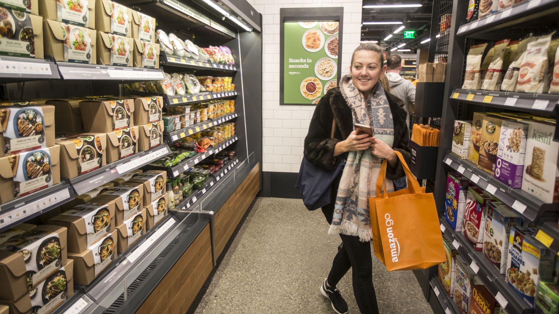 A women walks by a refrigerator case holding an orange Amazon Go bag