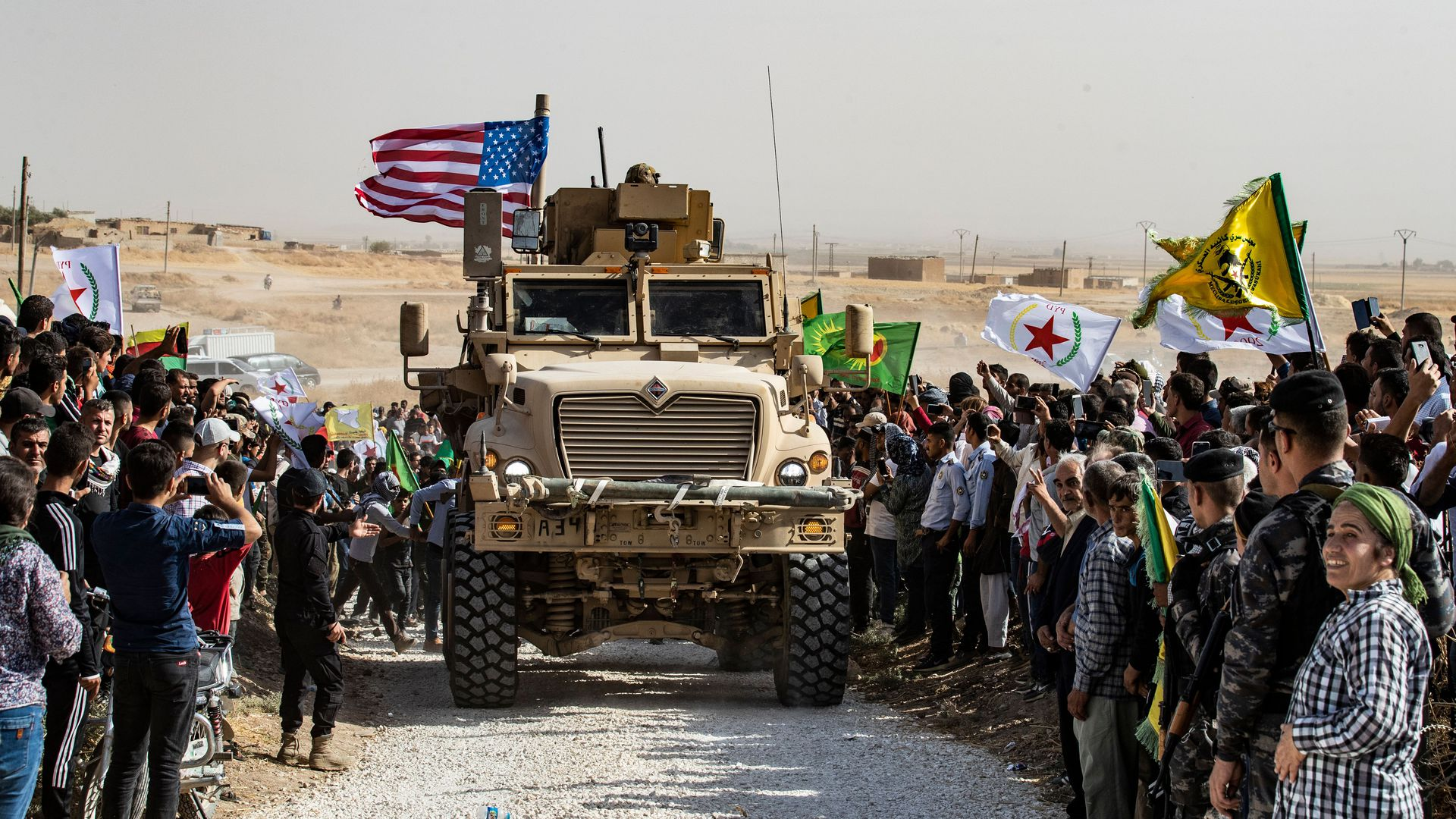 Syrians gather around a U.S. armored car
