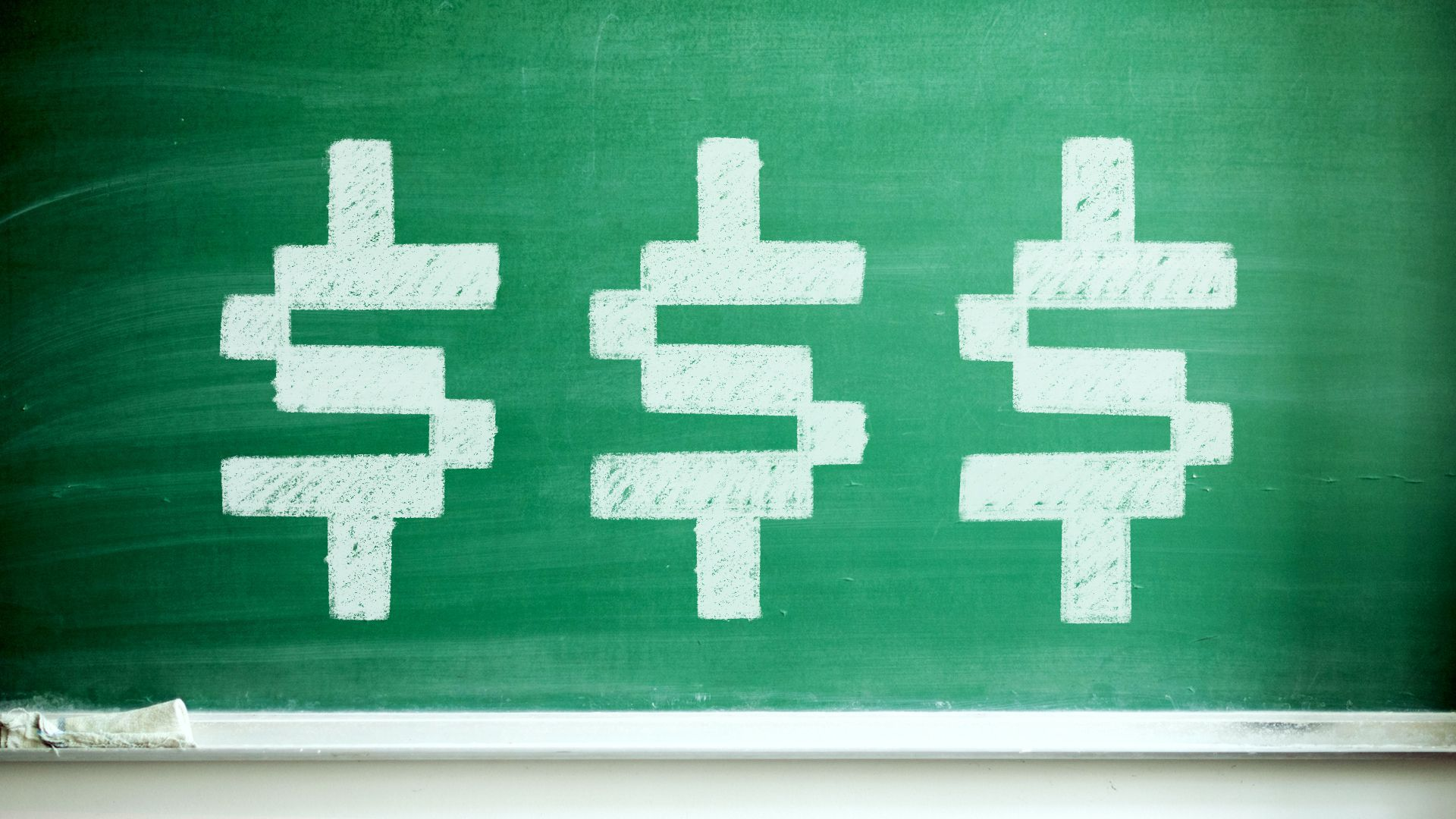 Illustration of a chalkboard with three digital-style dollar signs on it.