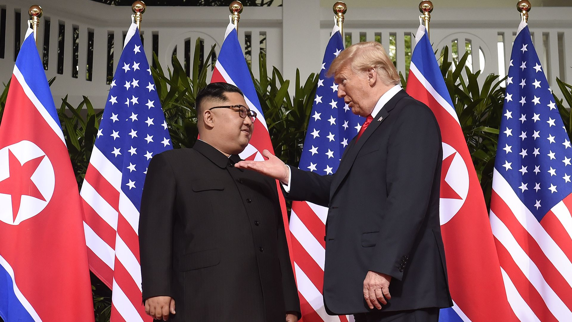Kim Jong-un and Donald Trump in front of flags