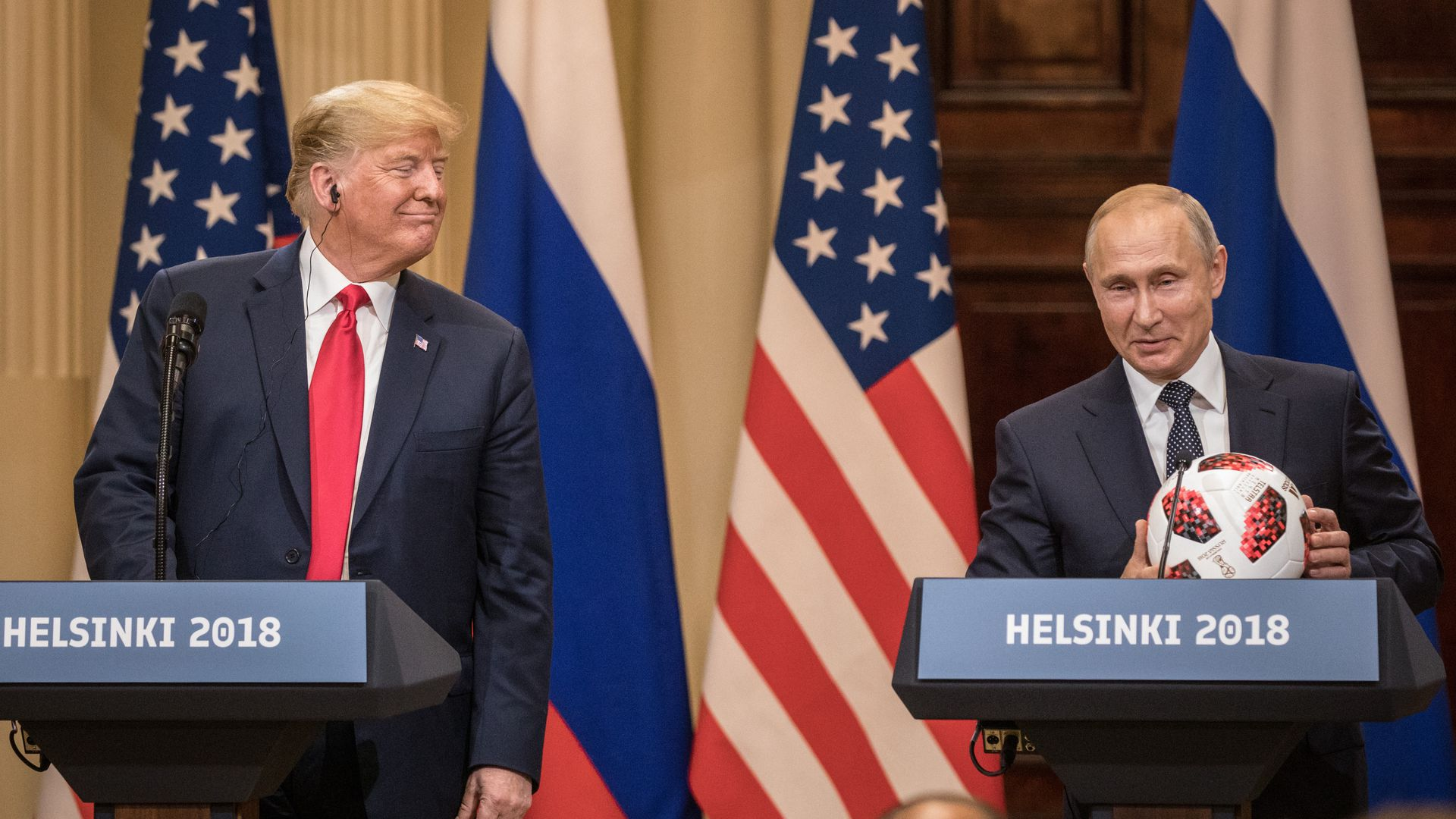 Trump smiles over at Putin, who's holding a soccer ball