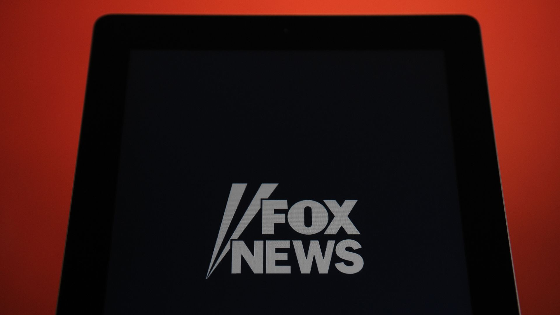 In this image, a large black screen displays the Fox News logo.