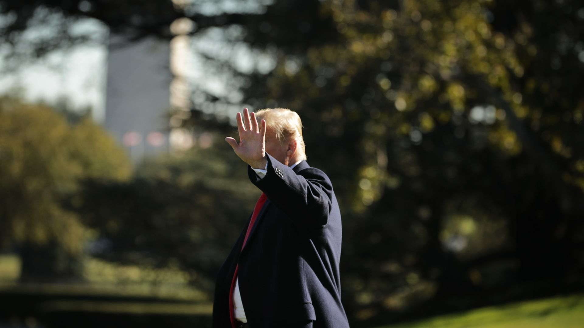 In this image, Trump waves at the camera while walking, which blocks out his face. The Washington Monument can be seen behind him.