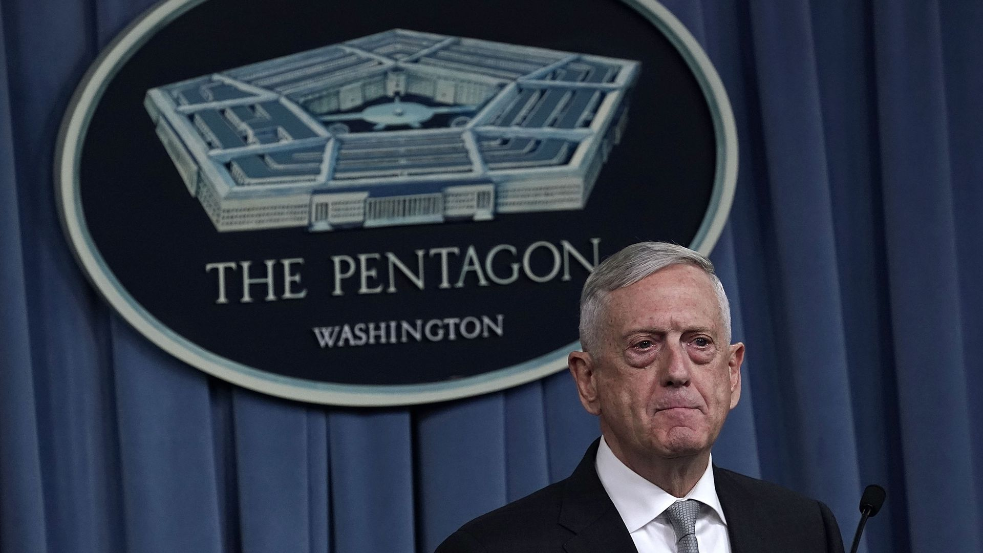 Defense Secretary Mattis stands in front of Pentagon sign.