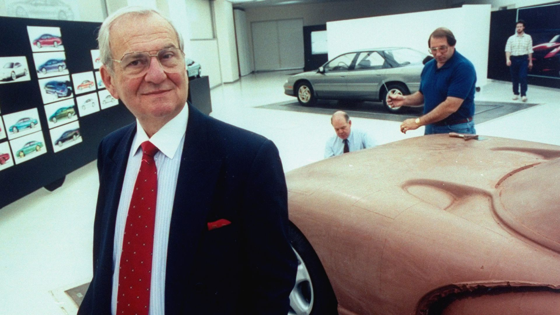 Chrysler Corp. Chmn. Lee Iacocca posing in front of full-sized clay model of the proposed Viper sports car being worked on by staff technicians.
