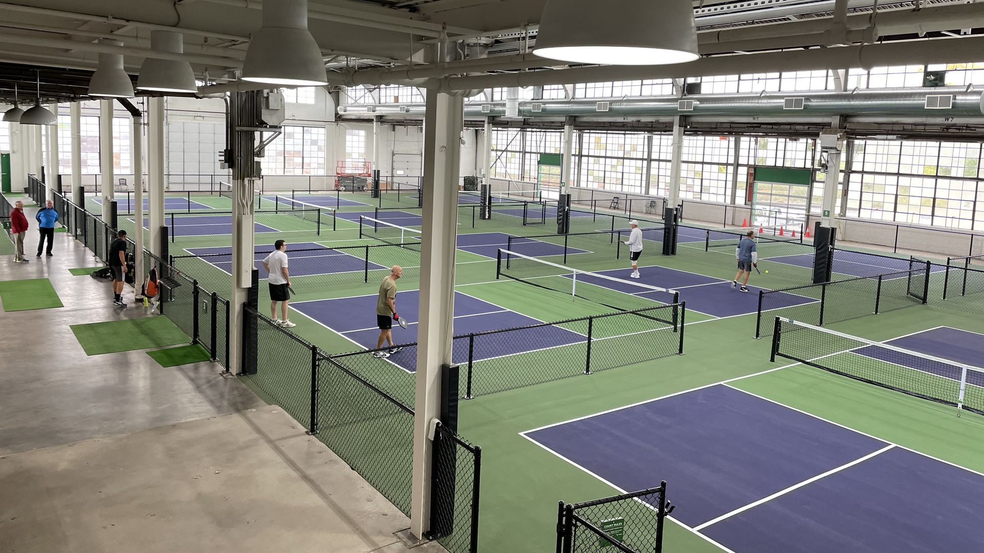 Groups of people play pickleball on pickleball courts
