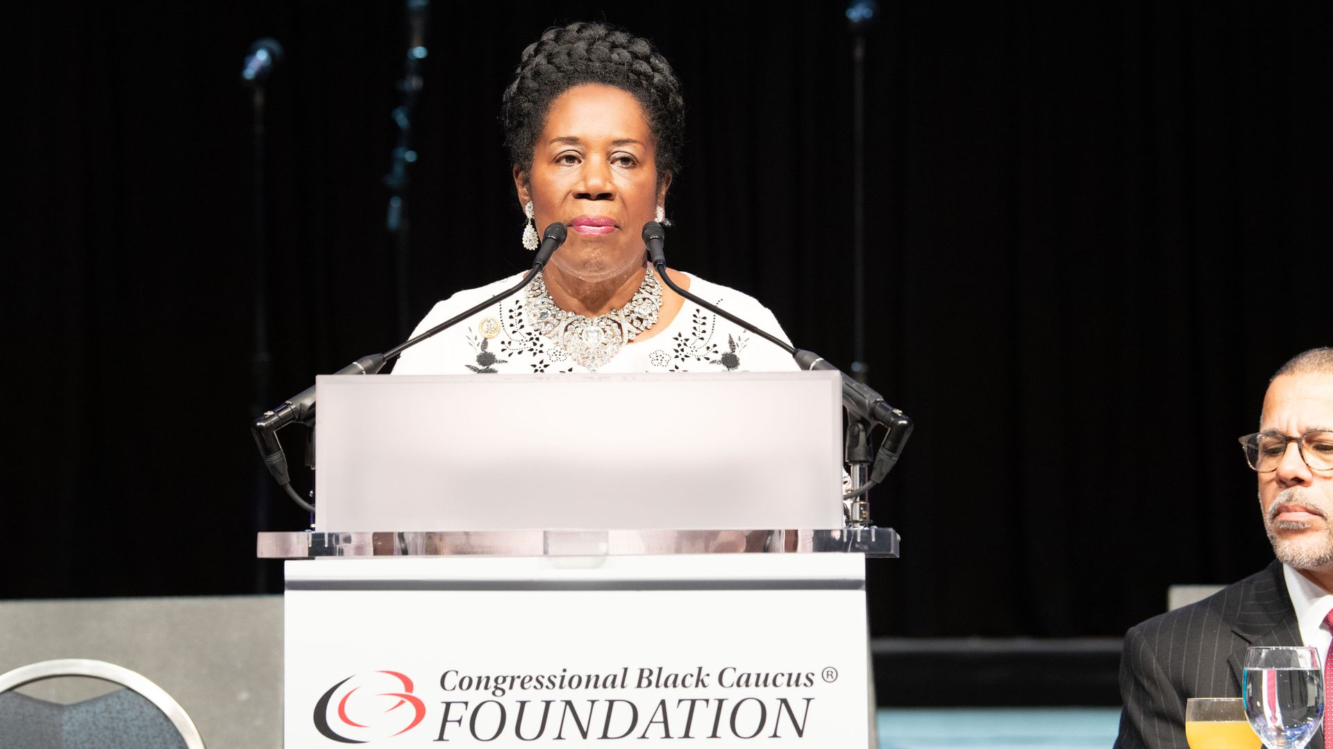 Sheila Jackson Lee at CBC Foundation podium in all white.