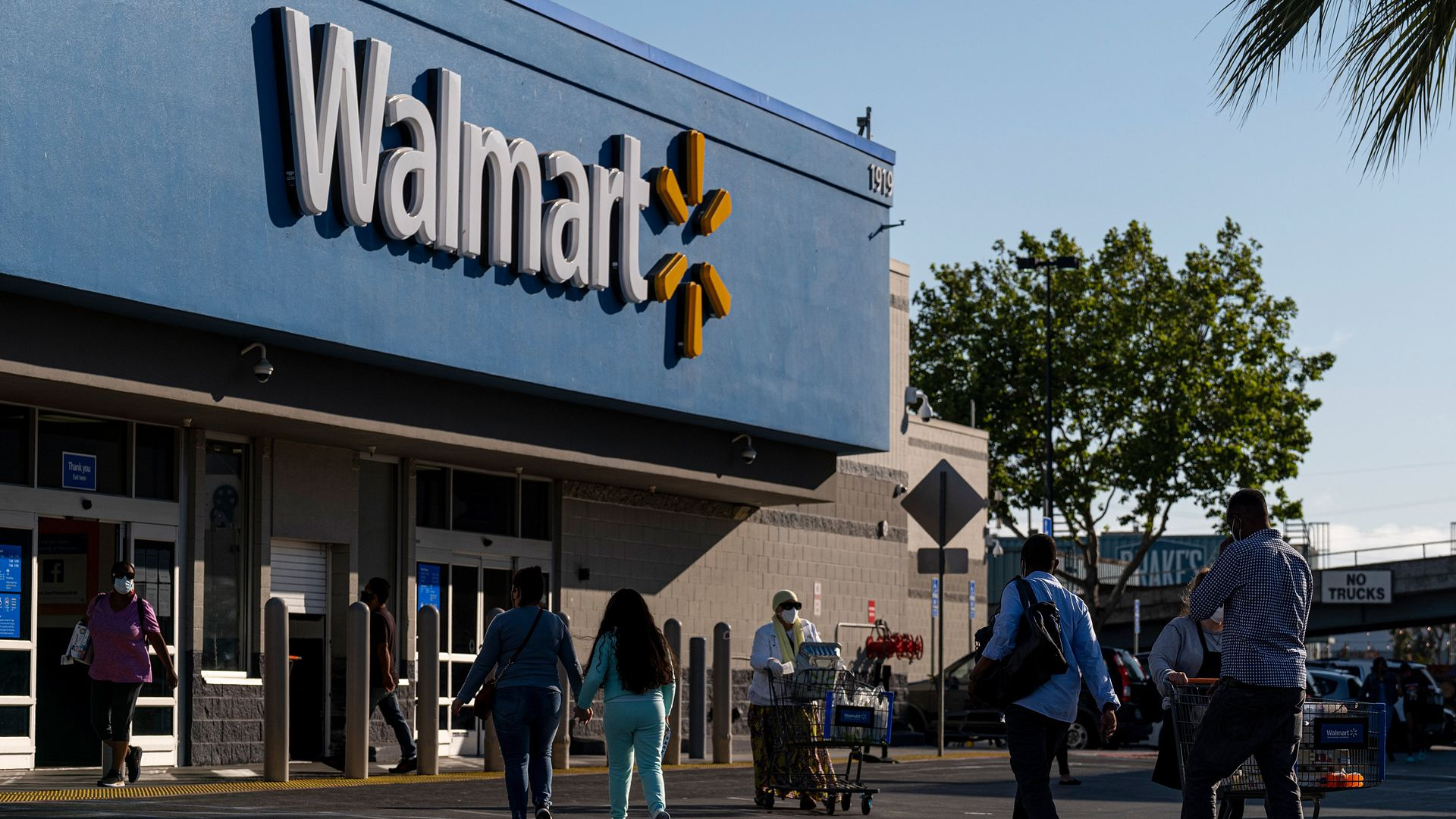Shoppers walk in front of a Walmart store in San Leandro, California in May.
