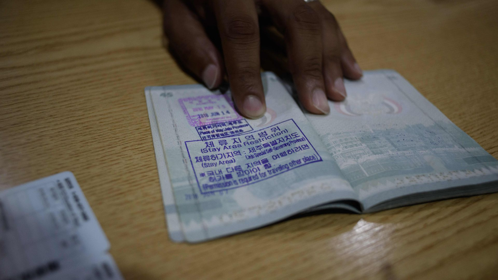 A hand holding open a foreign passport with a stamp in Korean