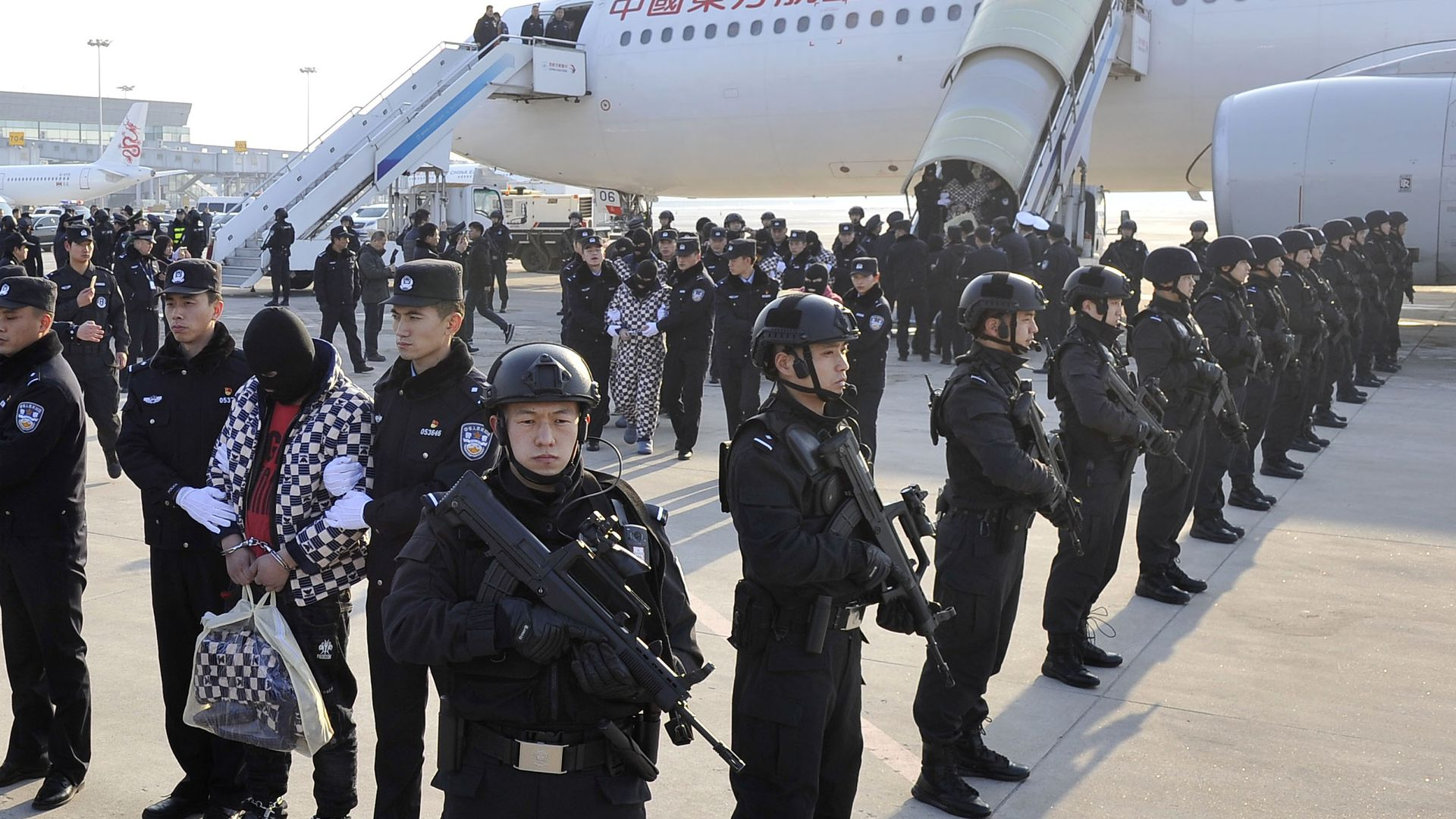 104 telecom fraud suspects returned to China under police escort at airport strip.