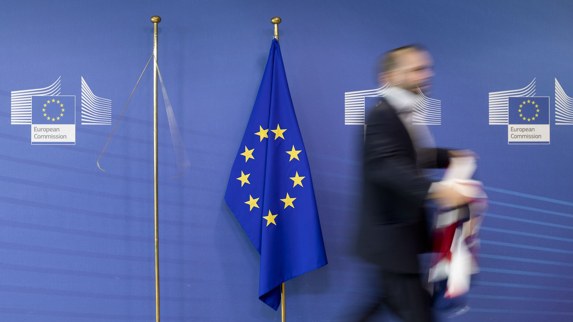 The flag of the European Union with a man walking away from it holding the Union Jack