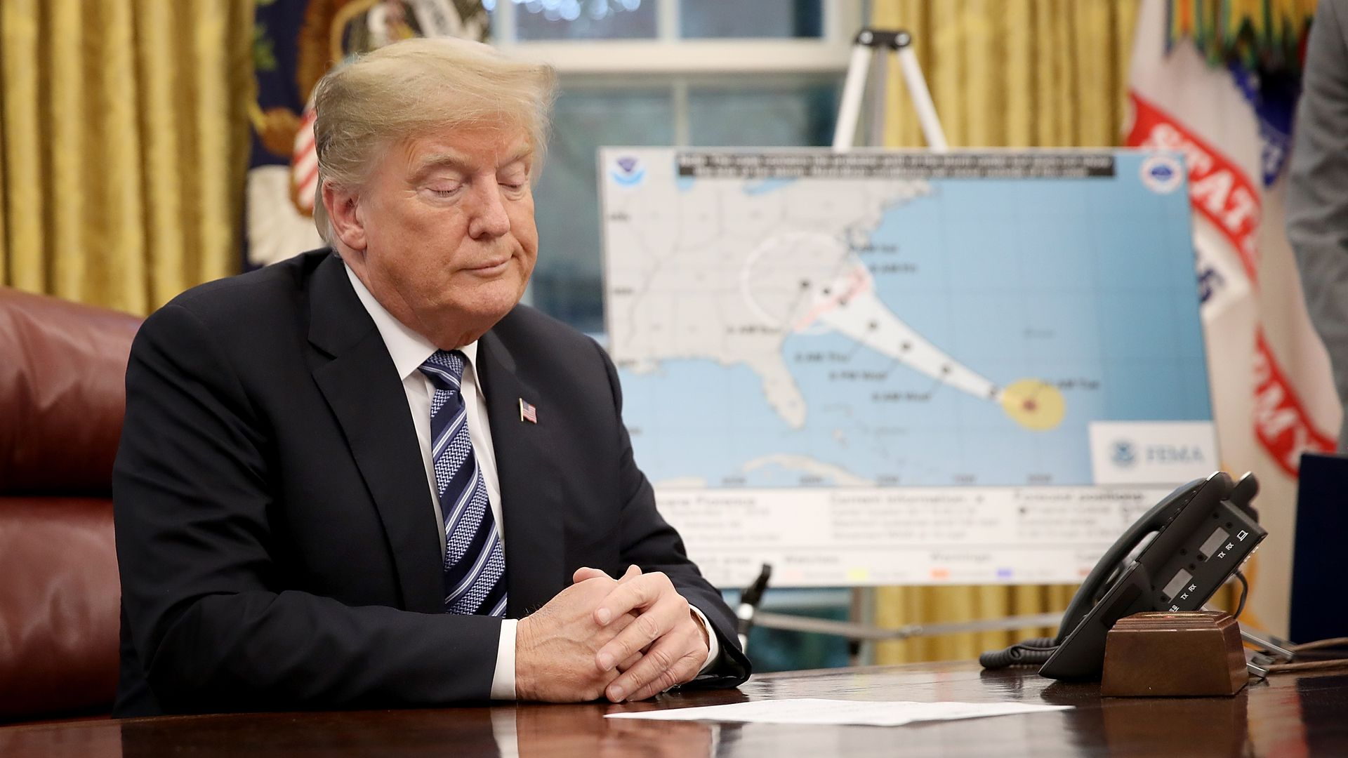 Trump sits as his desk during a meeting about Hurricane Florence