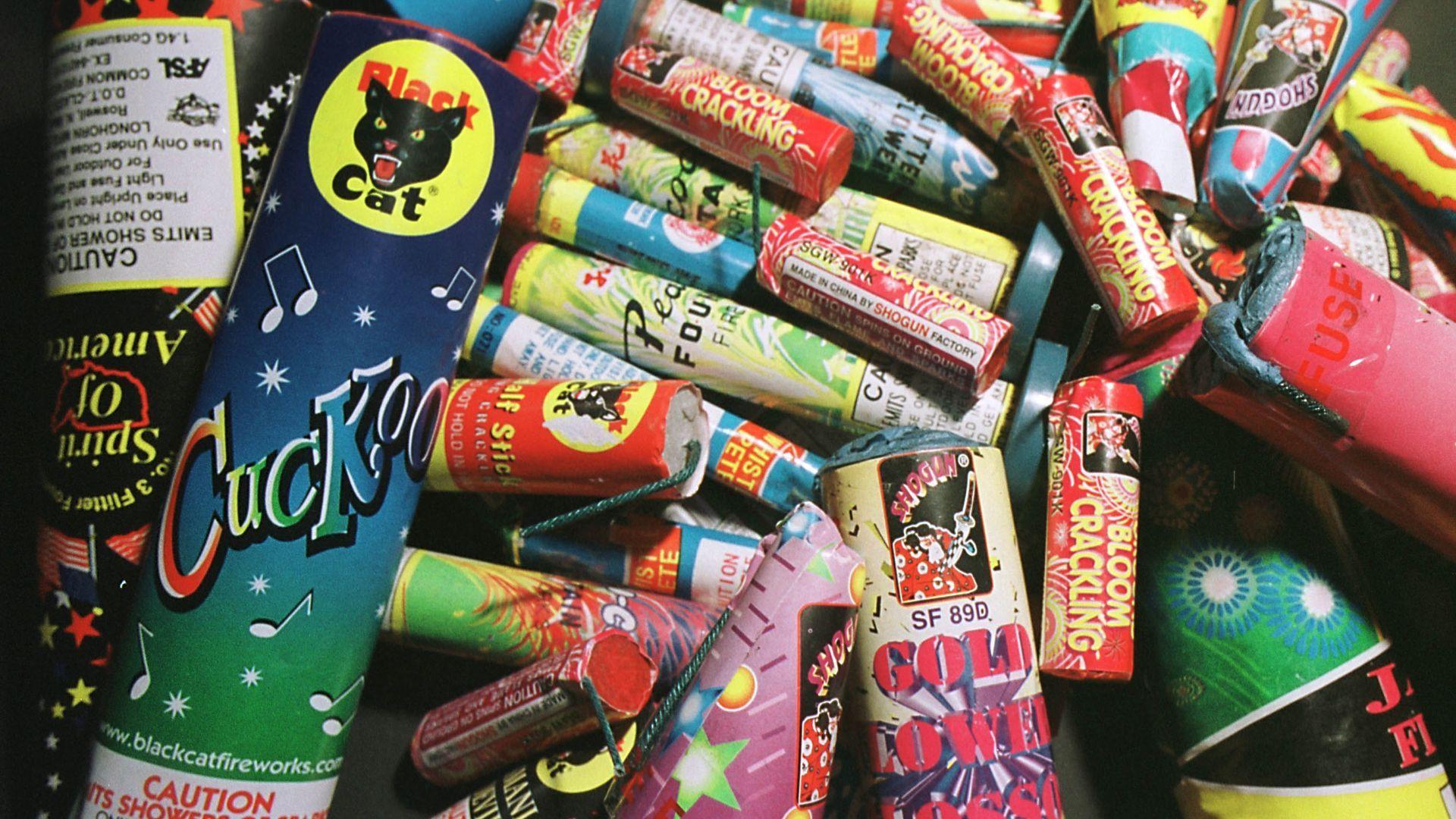 Dozens of colorful bottle rocket fireworks for sale.