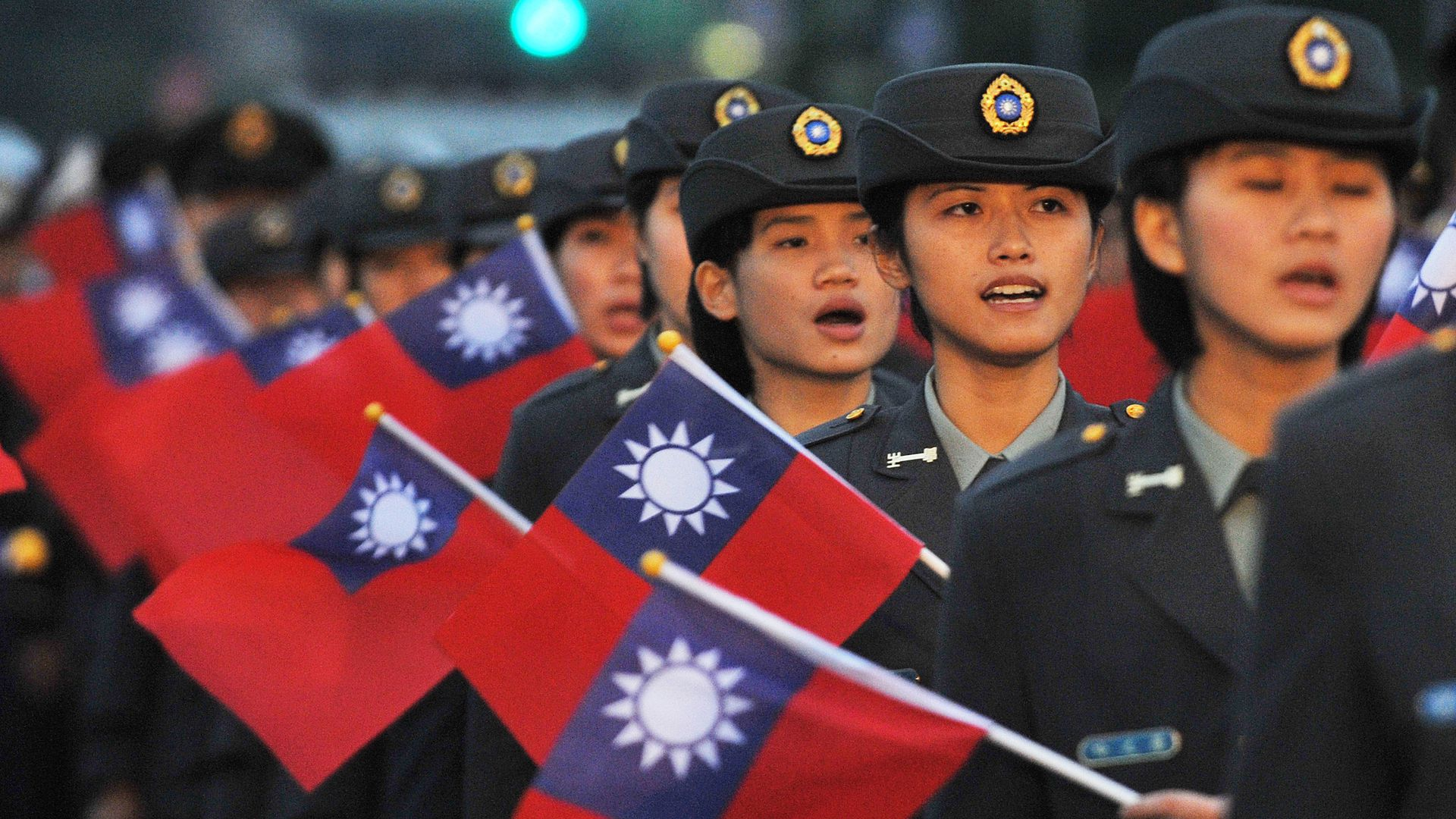 Young women in military uniforms carry Taiwanese flags