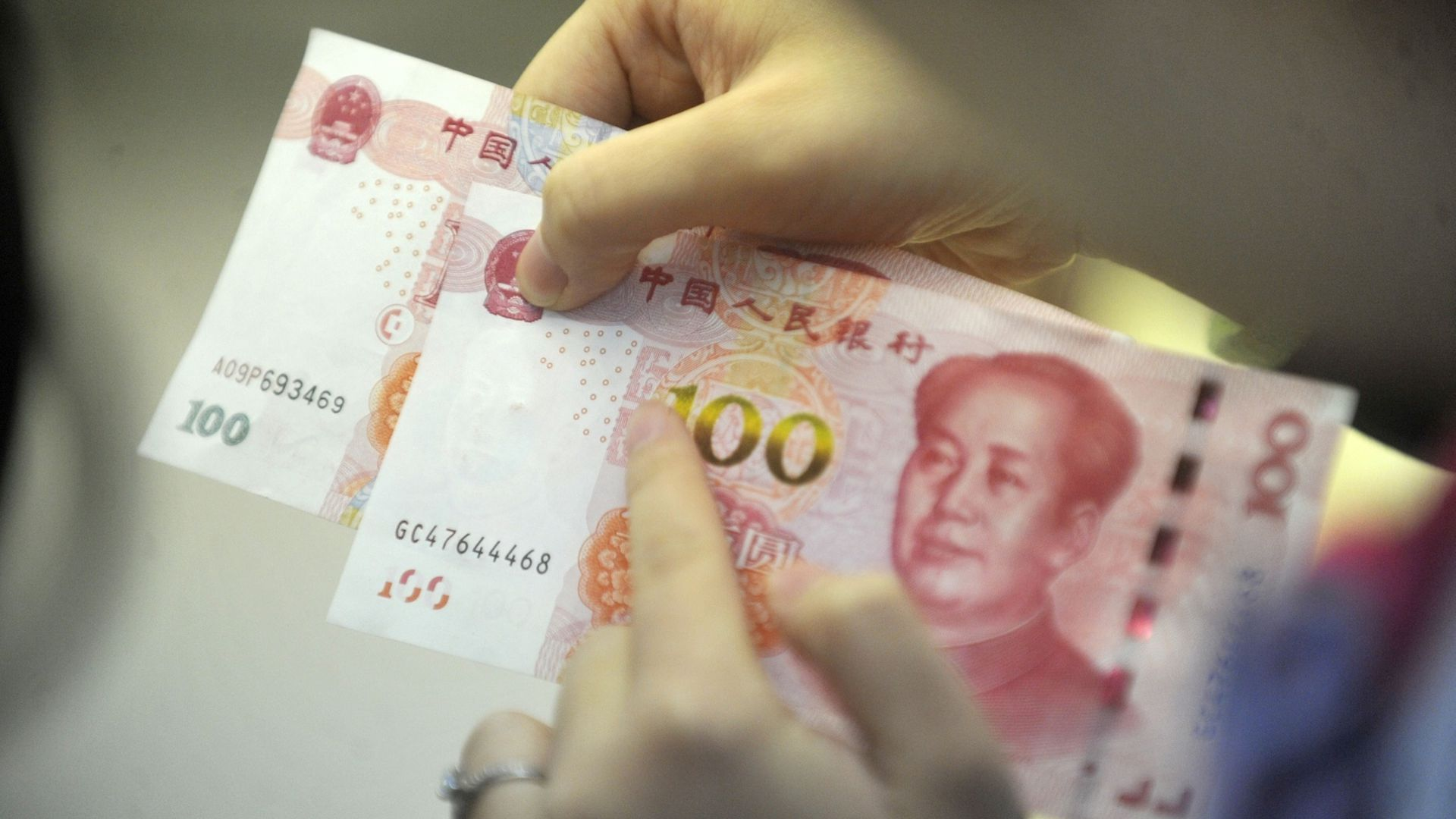 A person holds two 100 yuan notes