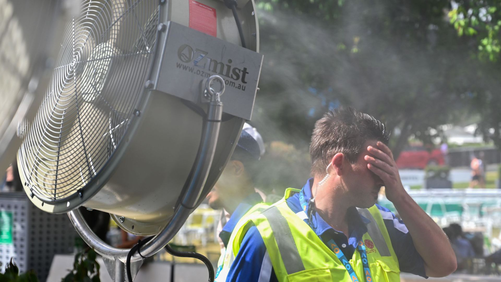 A man cools down in front of a mist fan for relief from the hot weather in Melbourne, Australia.