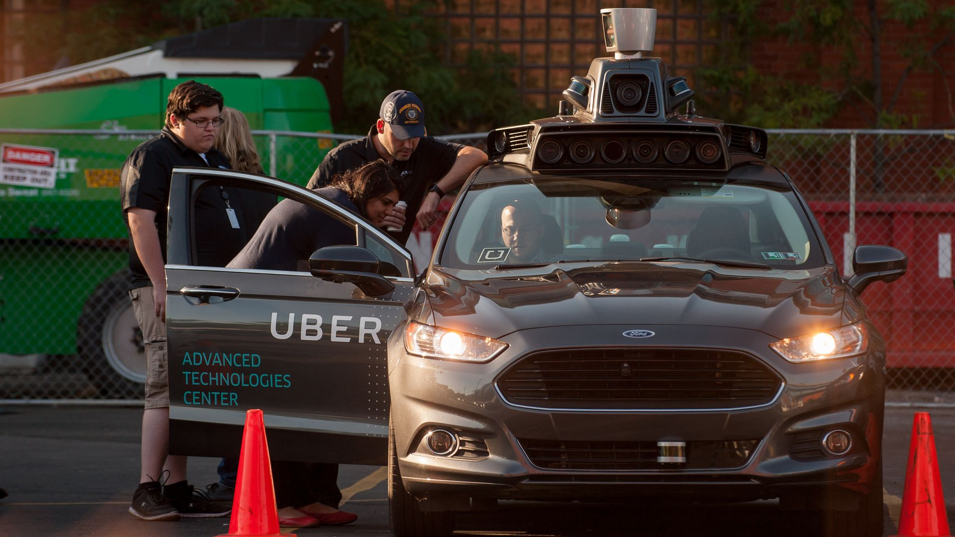 people crowd around a self-driving Uber vehicle in a parking lot