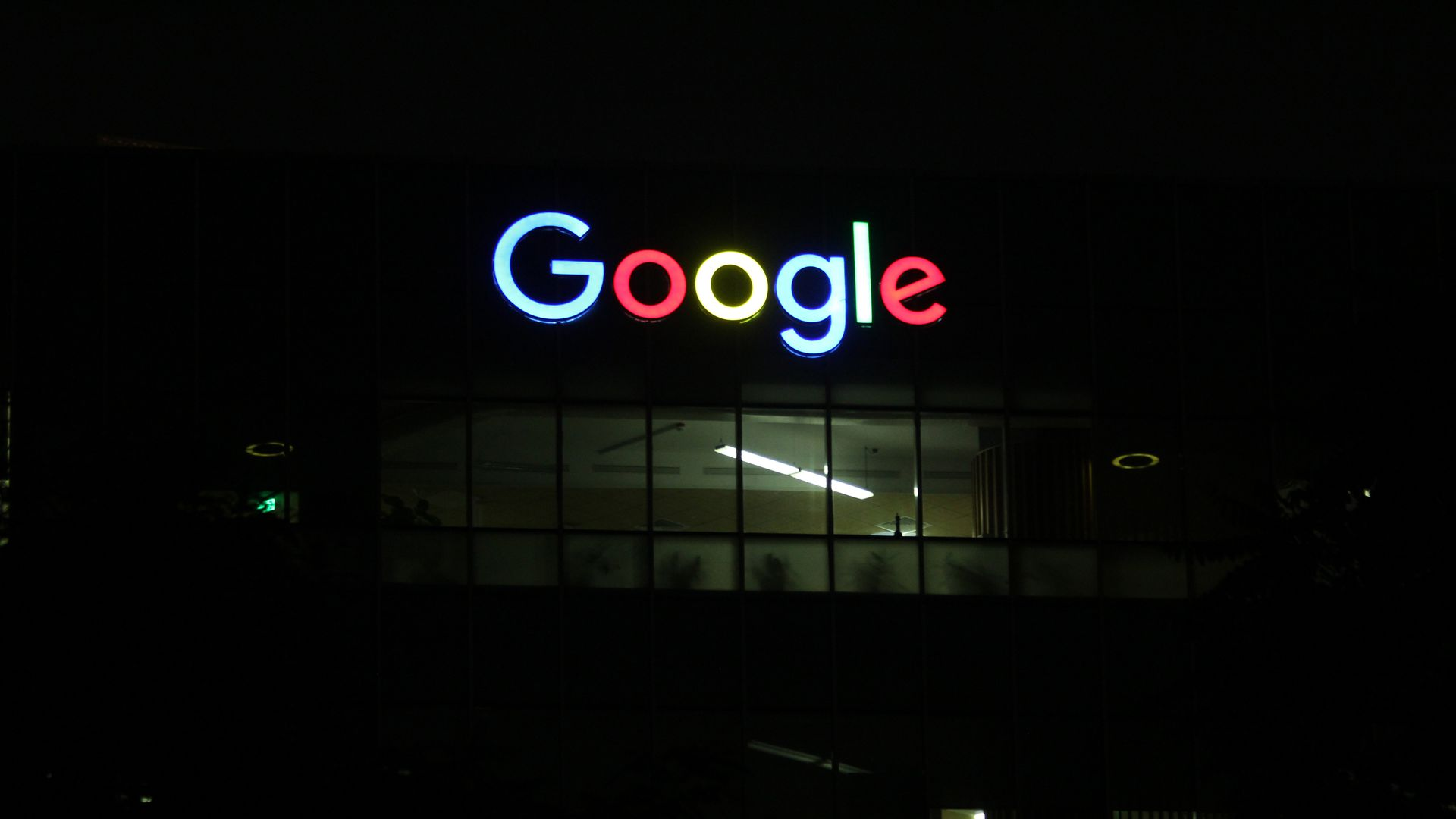 Google logo lit up outside building in the dark