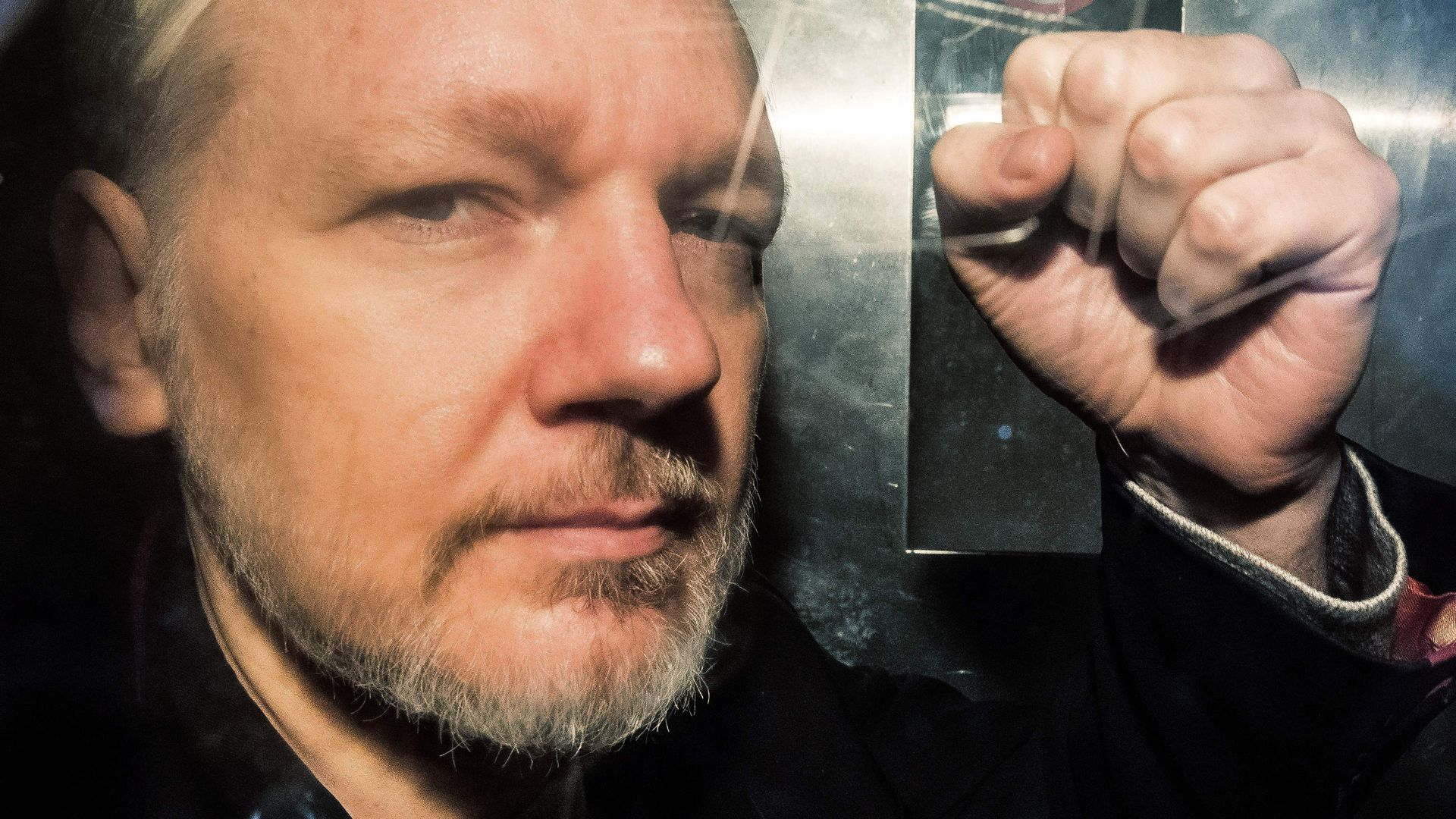 Julian Assange holding up a fist while looking into the camera.