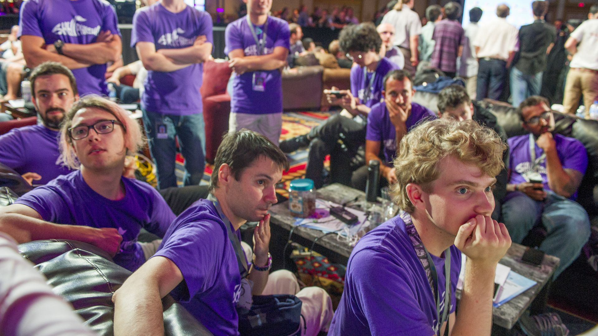 Hackers watch their system perform in a competition