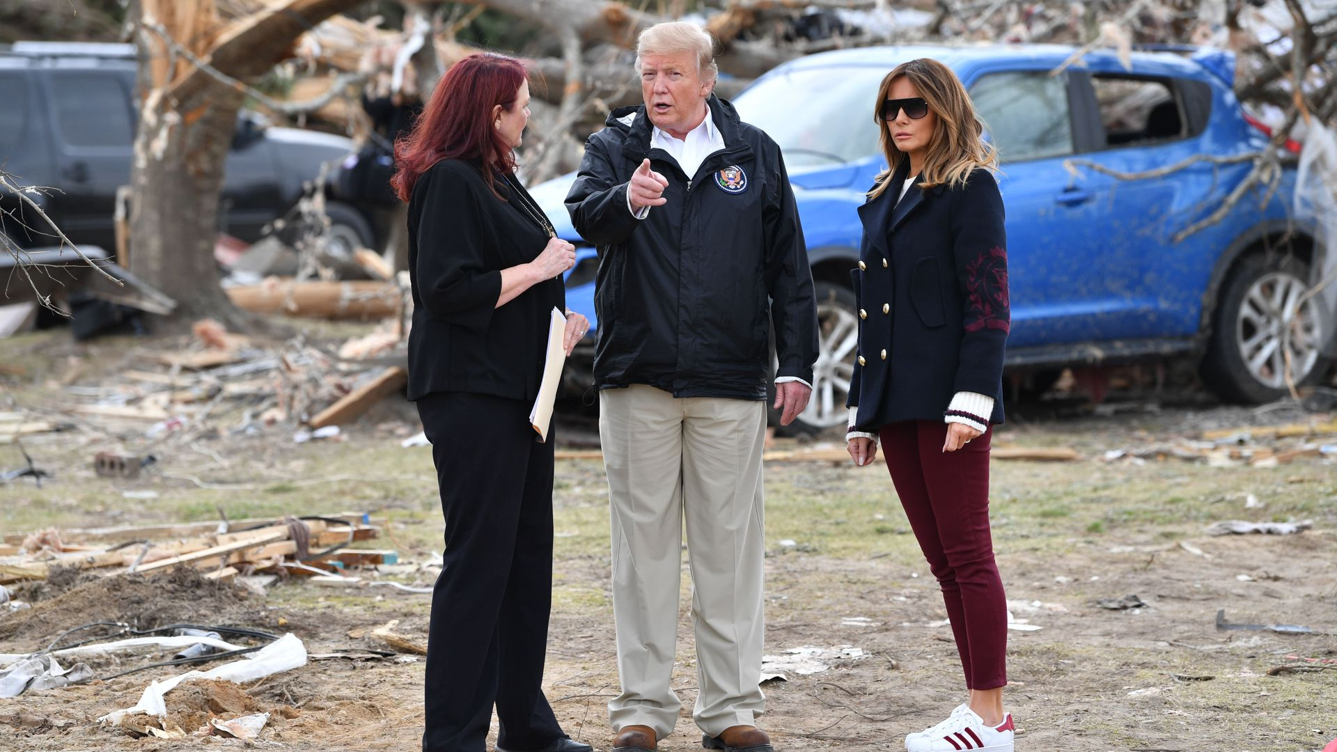 President Trump and wife Melania Trump stand next to a woman in front of rubble from a tornado in Alabama.