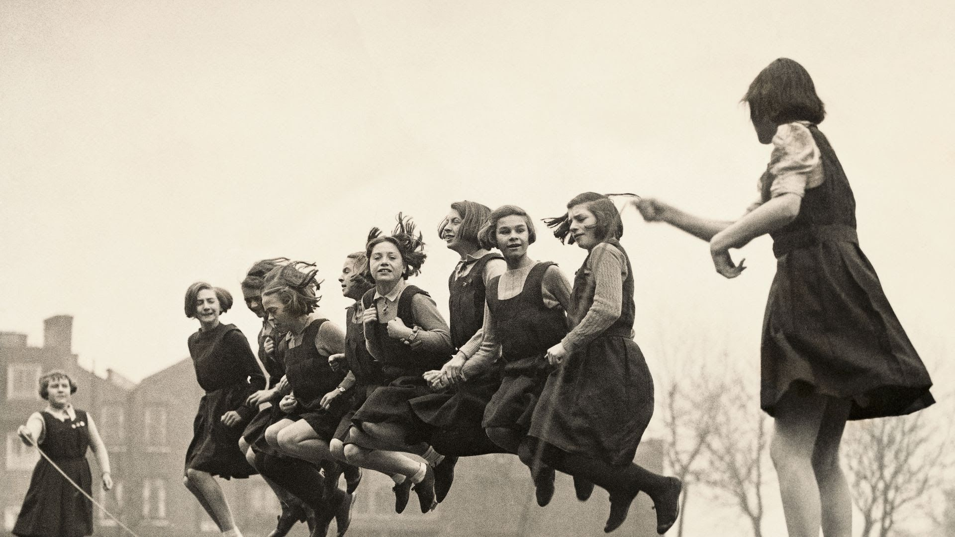 A black and white photo of schoolgirls in uniform jumping rope