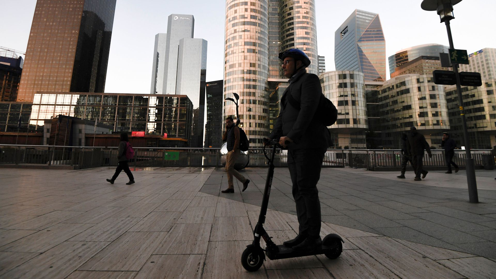 In this image, a person rides an electric scooter through a mostly empty city quad. Skyscrapers are in the background.