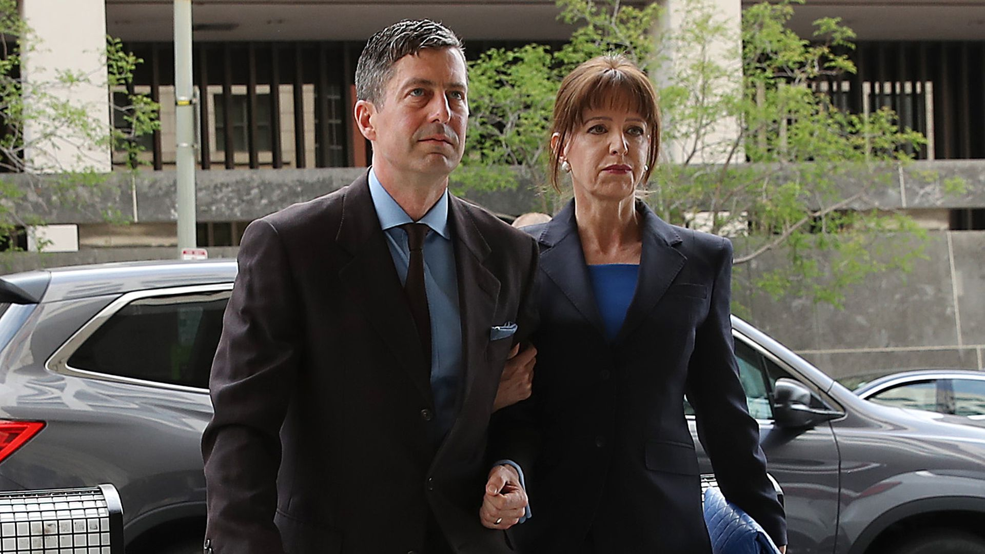 In this image, Sam Patten and his wife walk out of a sedan car with elbows linked.