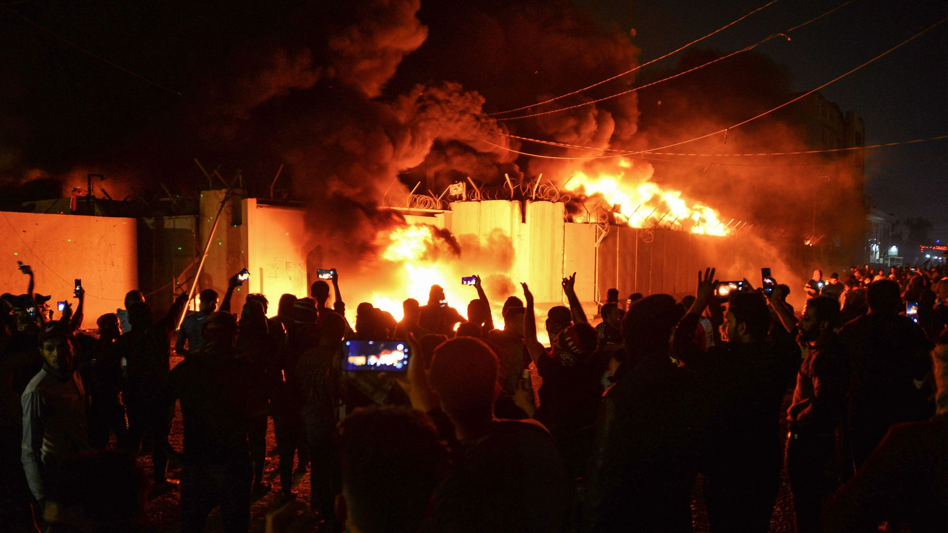 Iraqi demonstrators gather as flames start consuming Iran's consulate in the southern Iraqi Shiite holy city of Najaf
